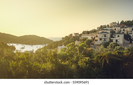 View of resort town houses on hill near sea with lots of green foliage and boats on water in distance - Sivota, Greece