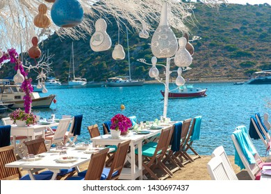 Blick auf Restaurant oder Café und Bougainvillea Blumen am Strand in Gumusluk, Bodrum Stadt der Türkei. Die Stühle, Tische und Blumen im Stil der Ägäis in Bodrum in der Nähe des schönen Ägäischen Meeres.