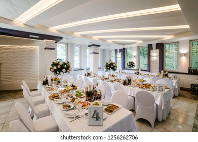 View of the restaurant hall. Festive table decorated composition of flowers, greenery, candles in wedding banquet hall. Table newlyweds covered with tablecloth.