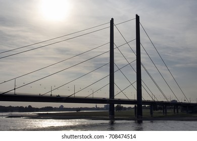 View of Rheinkniebrucke bridge and Rhine river with back light in Dusseldorf.