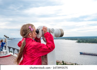 View from the right bank of the Volga River, A little girl looks at the ships on the Volga from the observation deck above the Chkalov stairs, Nizhny Novgorod, Russia