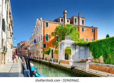 View of the Rio Marin Canal and scenic facades of old medieval houses in Venice, Italy. The Ponte Cappello dei Garzoti is visible in background. Venice is a popular tourist destination of Europe.