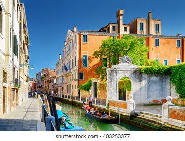View of the Rio Marin Canal and scenic facades of old medieval houses in Venice, Italy. Tourists traveling in gondola. The Ponte Cappello dei Garzoti is visible in background.