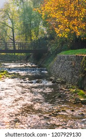 View of a river or creek with small waterfalls and a wooden bridge in autumn. Samobor near Zagreb, Croatia.