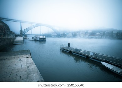 View of the River Douro and the metal bridge of Don Luis in Porto. The fog. Toned.