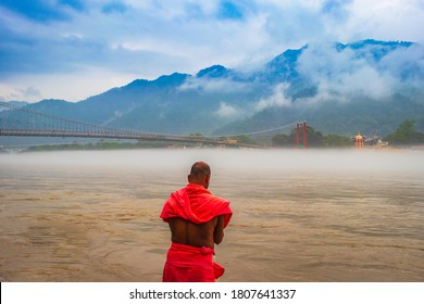 view of River Ganges, the famous bridge Ram Jhula surrounded by temples and mountains around in Rishikesh, India