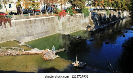 View to the river Isar in fall, man is fishing, Munich, Bavaria