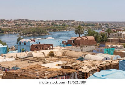 View of river Nile in Aswan Egypt from riverbank through rural countryside landscape with traditional Nubian village houses in foreground