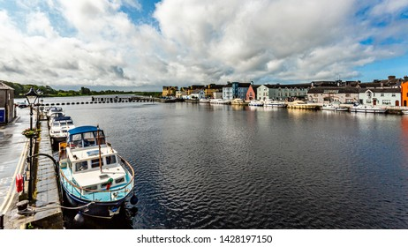 View of the river Shannon with boats anchored on the coast and picturesque houses in the town of Athlone, wonderful and relaxed day in the county of Westmeath, Ireland