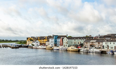 View of the river Shannon with boats anchored on the coast and the town of Athlone with picturesque houses, wonderful and relaxed day in the county of Westmeath, Ireland