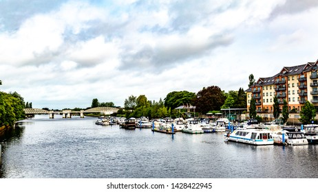 View of the river Shannon with boats anchored at the dock with the railway bridge in the background in Athlone town, wonderful and relaxed day in County Westmeath, Ireland