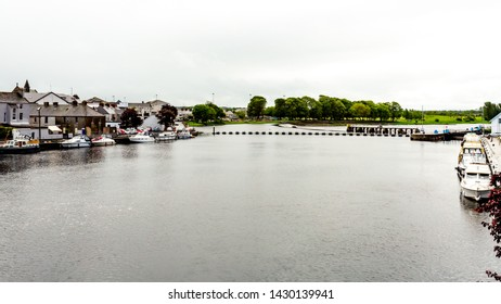 View of the river Shannon with boats anchored on the shore with a park with in the background in the town of Athlone, wonderful and relaxed day in the county of Westmeath, Ireland