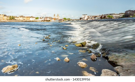 View of the river Shannon with its crystal clear waters and stones on the shore with the town of Athlone in the background, wonderful cloudy day in the county of Westmeath, Ireland
