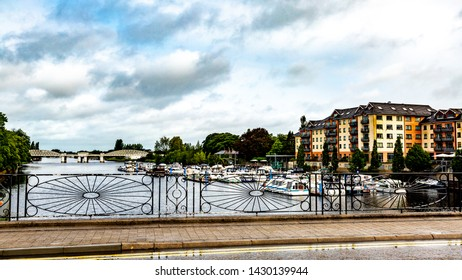 View of the river Shannon through the fence of the blacksmith, boats anchored at the dock with the railway bridge in the background, town of Athlone in the county of Westmeath, Ireland