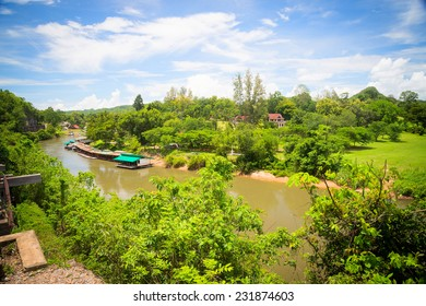 The view of the river. Small houses on the river. Blue sky with clouds.