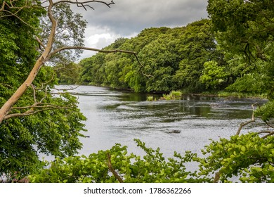 A view of a river through a gap in trees in summer, on the River Dee, Galloway, Scotland