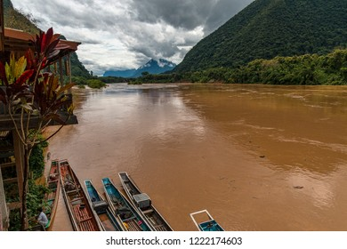 View from River Village of Traditional Fishing Skiffs, Rain Forest, Cloudy Skies, and Green Jungle Mountains. (Muang Ngoi, Nam Ou River, Laos).