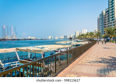 view of riverside promenade in Sharjah with Al Maghfirah mosque at background, UAE