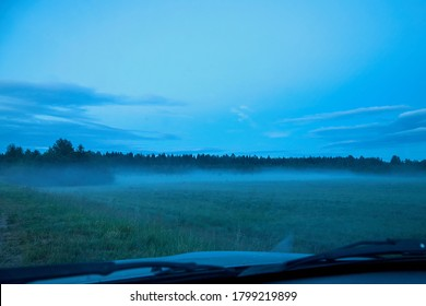 View from the road to a field with fog late in the evening or at night