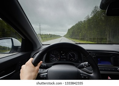 View of the road from inside car in the windshield in rainy weather. Man's hand drive vehicles