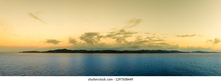 View of Roatan Island at first light, seen from the deck of a ship.