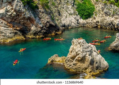 View from the rock cliffs of kayaker exploring the crystal clear Mediterranean waters of a cove off the coast of Dubrovnik, Croatia