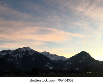 view of rock mountains with snow on the top and pastel sky in the background at Interlaken, Switzerland