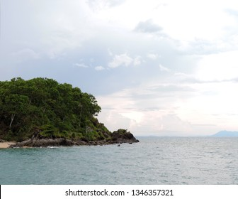 View of the rocks at Palm Cove Beach overgrown by palm trees and other tropical plants with view out over the ocean and the Great Barrier Reef in Cairns, Queensland, Australia