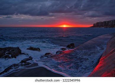 View from Rocky beach Valletta towards Sliema over a mighty seascape with blood red sun, powerful waves and pier leading to the city of Sliema.