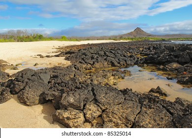 View of a rocky coast, red crabs, and Dragon Hill in the background of Santa Cruz Island, Galapagos National Park, Ecuador