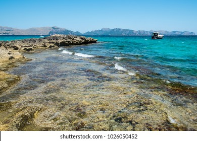 View of a rocky coast in sunny summer day. Sea waves on wild stone beach in Mallorca, Spain