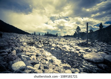 View from Rocky Mountain National Park in Colorado with stream over rock landscape, mountains and ominous sky. Image has vintage tone filter.