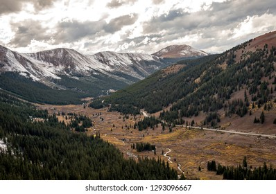 A view of the Rocky Mountains on a beautiful scenic byway towards Aspen, Colorado. An early winter storm has dusted the tops of the peaks with snow on this mid autumn day near Independence Pass.