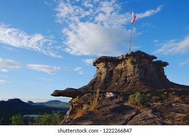 View of the rocky or stone mountain a nutural viewpoint with the flag of Thailand on the top with blue sky background.