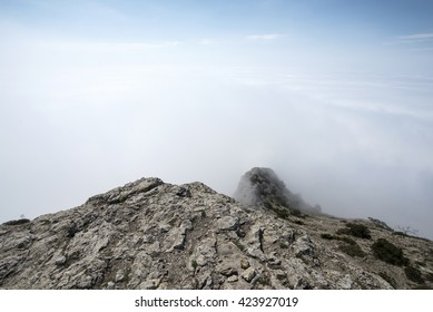 View from the rocky top of the mountain above the clouds. Crimea, Sudak