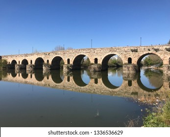 View of the Roman bridge of Merida with its reflection on the Guadiana river. Merida. Spain