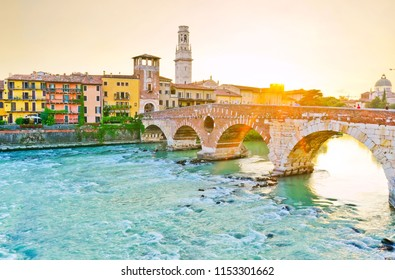 View of the Roman Ponte Pietra across Adige river at sunset in Verona, Italy.