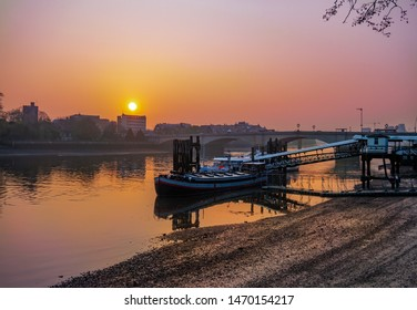 View of romantic scene in Putney bridge area at sunrise, with colorful sky reflected in Thames river in London