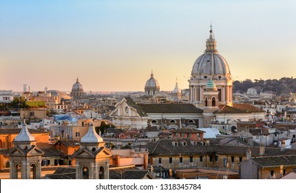 View of Rome from the Pincho hill. Panorama of the city center at sunset. Tiled roofs of houses, the dome of St. Peter. Sunset.