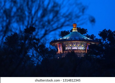 View of roof of Beijing's Temple of Heaven in evening with silhouette of trees