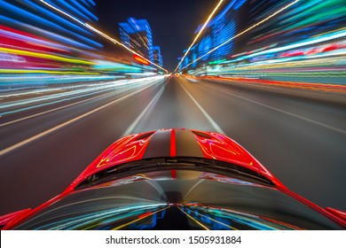 View from roof of the red muscle car Car moving in a night city, Blured road with lights with car on high speed. Concept rapid rhythm of a modern city.