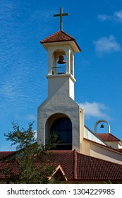 View of rooftop of Roman Catholic church showing bell tower, steeple, cross and two bells.