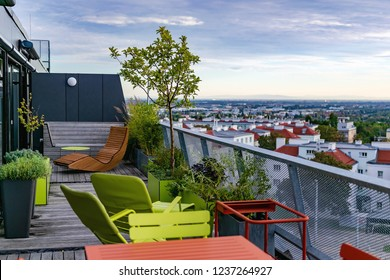 View from a rooftop terrace over southern Vienna - rooftop garden and chill-out area with a new rocking couch on an old wooden deck