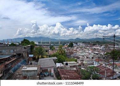 View of rooftops and green palm trees in cityscape of Santiago de Cuba with white fluffy clouds in blue sky