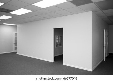view of a room inside of a room with blank walls and open doors in a vacant office building
