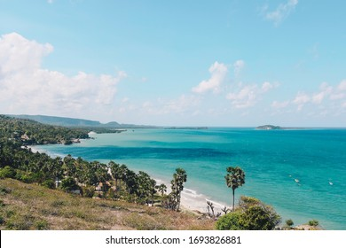 View of Rote Tropical Beach with deep turquoise blue ocean and small exotic island in the center in Rote Island, Indonesia.
