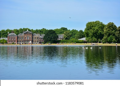 View of the Round Pond in Kensington Gardens, London, England. Kensington Palace, also seen on the photo, is an official residence of the British Royal Family