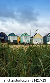 A view of a row of colorfully painted wooden beech huts through some green sand dune grasses. Set on a portrait format. Located in the South of England at Christchurch, Dorset UK.
