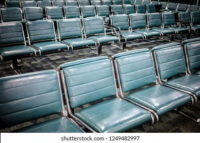 View of rows blue leather seats in waiting hall of modern airport