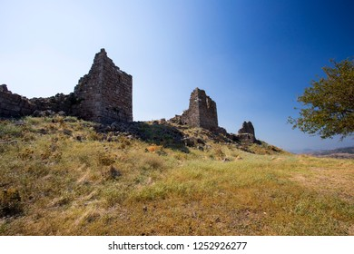 View of the ruined ancient fortress with three watchtowers against the sky.